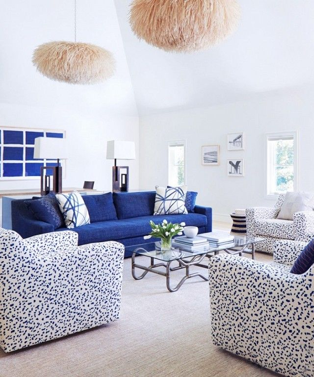An Airy Living Room With A Navy Blue Sofa, And Textured Pendant Lights