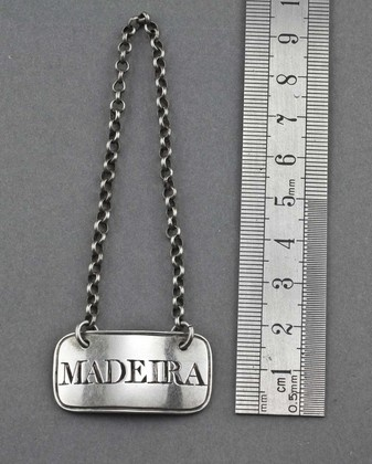 """A Georgian silver wine label, engraved """"Madeira"""", by Daniel Hockly. The label is rectangular with a reeded border, and has its original chain. It is fully hallmarked, the hallmakrs are clear. Hockly emigrated to the Cape Colony as part of the 1820 Settlers, where he continued working as a silversmith, also using a DH makers mark. Hockly is mentioned as one of 5 wine label makers worthy of mention for the quality of their product amongst the new generation of specialists (Wine Labels…"""
