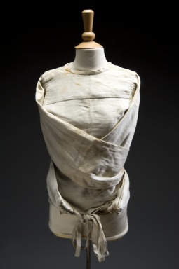 This straitjacket restrained adult patients in psychiatric hospitals during the 1930s through to the 1960s. It is made of heavy canvas. It has four ties on the main body and excessively long arms. These wrap around and tie behind the back. Such garments restricted the movements of patients considered violent or unruly. Their use was phased out when anti-psychotic drugs and more 'humane' methods of management were introduced.