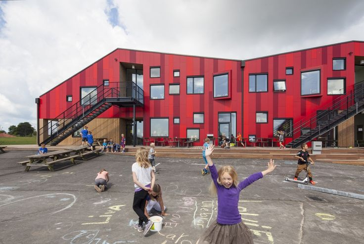 The Vibeeng School / Arkitema Architects, kids playing, vertical red wall paneles, square windows, exterior stairs, wood deck