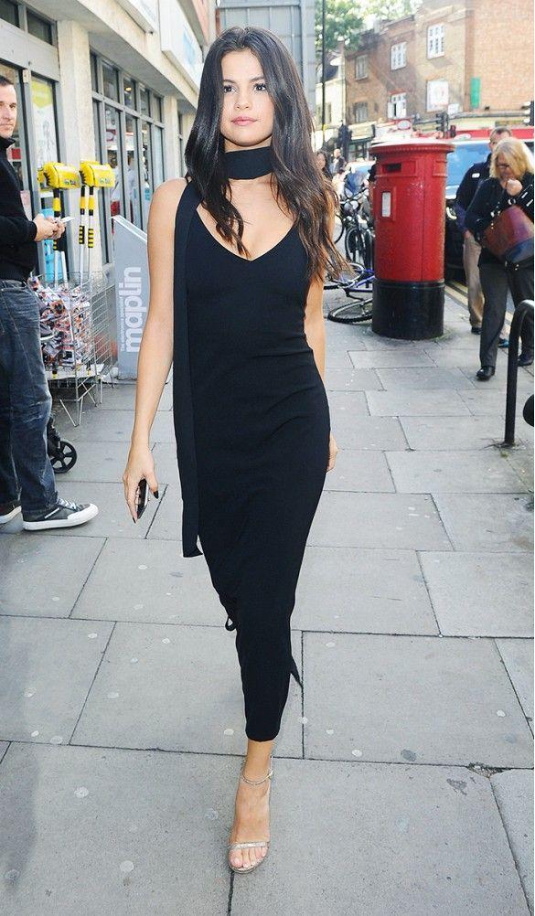 Selena Gomez wears a black slip dress, skinny silk scarf, and metallic heels