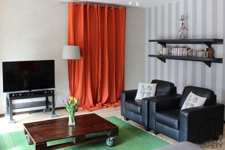 Pokój telewizyjny, stolik z palet, tapeta w szerokie, szare pasy
