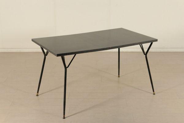 Tavolo allungabile; struttura in metallo con puntali in ottone, piano in legno ricoperto in formica. Discrete condizioni, presenta alcuni segni di usura.