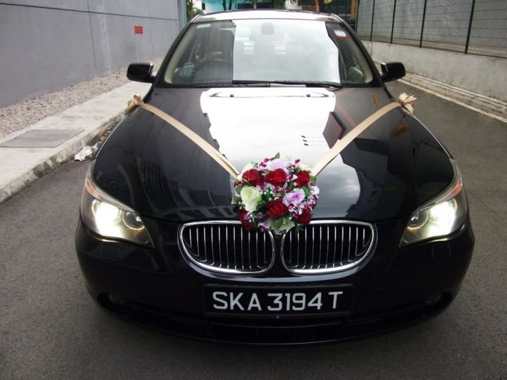 bouquet de roses rouges et blanches et orchidées fixé sur le capot de la voiture mariage