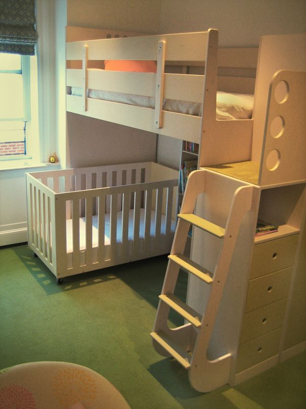 This design is ideal when there is an age difference of at least five years between siblings. Two sisters, a six-year-old and baby, share this room. The specially designed crib is set low to the ground to maximize space beneath the bottom of the loft and access to the child in the crib. The bunk bed features a landing that slows a child as he or she moves up and down the stairs for added safety.