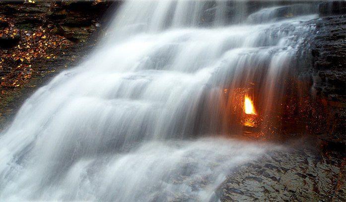 """Рядом с городом Баффало, недалеко от озера Эри находится удивительный водопад. Потоки воды перекрывают вход в небольшой гротик, в котором бьется пламя вечного огня. На глубине 400 метров здесь залегает природный газ, просачивающийся на поверхность. Если огонек гаснет, то его заново поджигают либо электрические разряды гроз, либо заботливые туристы. Посетившим это место остается пройти только """"медные трубы""""."""