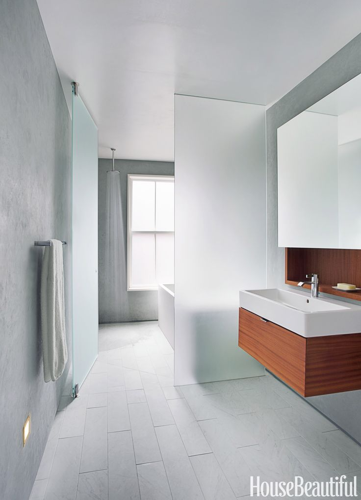 In a soothing, fluid bathroom in Boston, Massachusetts, designed by Pamela Butz and Jeffrey Klug, a plane of frosted glass separates the wet side of the bathroom, with the open shower, from the dry side, with the sink. Hansgrohe's Downpour 180 showerhead makes you feel as if you're standing under a water fall. Vero sink by Duravit. IMO faucet by Dornbracht. Towel bar by Samuel Heath.   - HouseBeautiful.com