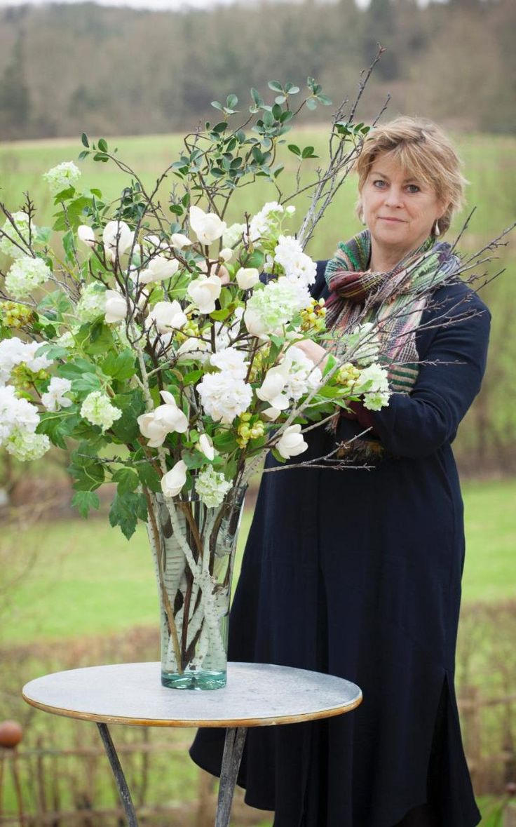 Sarah Raven arranging faux spring flowers in glass vase                                                                                                                                                      More