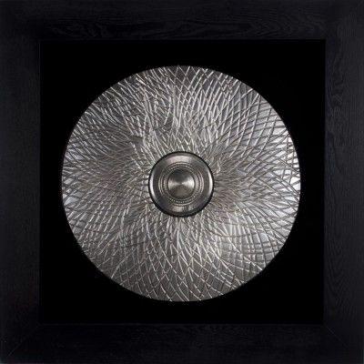 Obraz przestrzenny Shield zawiera piękną, współczesną kompozycję, która znajdzie uznanie w oczach wszystkich, którzy cenią sztukę nowoczesną. Obraz złożony jest ze srebrnej tarczy wykonanej ręcznie z jednego kawałka drewna. Kompozycja przeciwstawia się czarnemu tłu i jest przytwierdzona do grubej ramy aranżując efekt unoszenia się w przestrzeni. Materały dopełniają się nawzajem by stworzyć idealną dekorację do każdej przestrzeni i wnętrza.