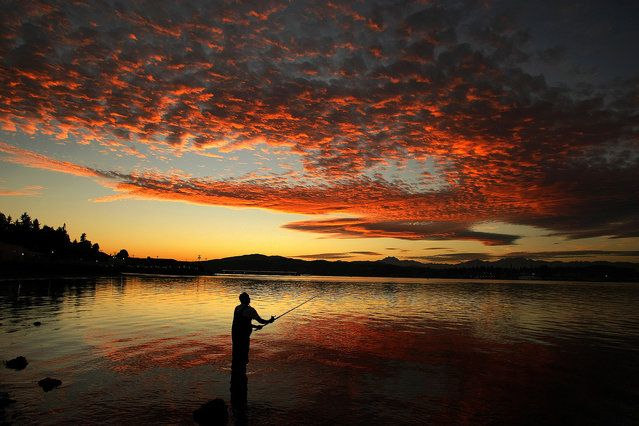 In this Friday, October 3, 2014 photo, Delmar Parris, of Port Orchard, Wash., casts his fishing line off Bay Street in Port Orchard during a fall sunset. (Photo by Larry Steagall/AP Photo/Kitsap Sun)