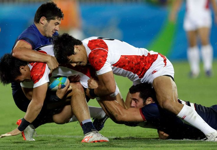 Bringing him down:    Japan's Teruya Goto, left, with teammate Shohei Toyoshima, top right, attack as France's Manoel Dall'igna, top left, deffends during the men's rugby sevens match on Aug. 10.