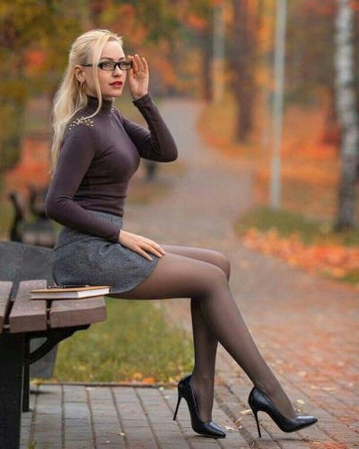 13834af912c Beautiful student girl with perfect legs sitting on the bench in the autumn  park.