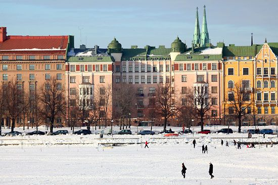 Helsinki in winter - people walking on sea ice in Merisatama. In summer this spot is a harbour for hundreds of boats.