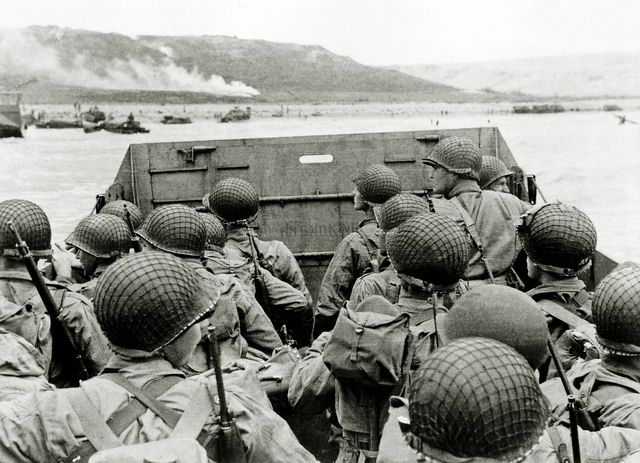 D-Day, Operation Overlord: U.S. soldiers watch the Normandy coast from a Landing Craft Vehicle, Personnel ( LCVP ) heading towards Omaha Beach Easy Red sector. Several vehicles are already present and white smoke can be seen in the distance. (June 6, 1944)