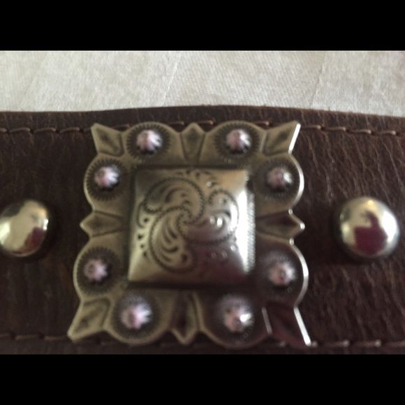 Leather bracelet Brown wide band leather bracelet with sterling silver charm that has lavender accents. Heart of a cowgirl Jewelry