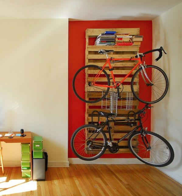 Bookcase, bike rack, red wall (and nine more ways to treat your bicycle like wall art from Treehugger).