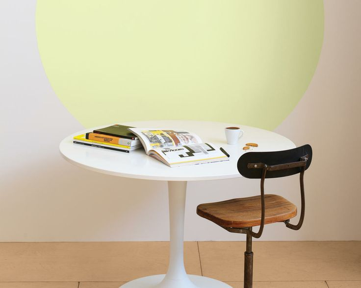 Jouez avec les effets de peinture colorés. Un simple cercle jaune peint sur le mur de cette salle à manger blanche attire l'œil et dynamise l'espace.