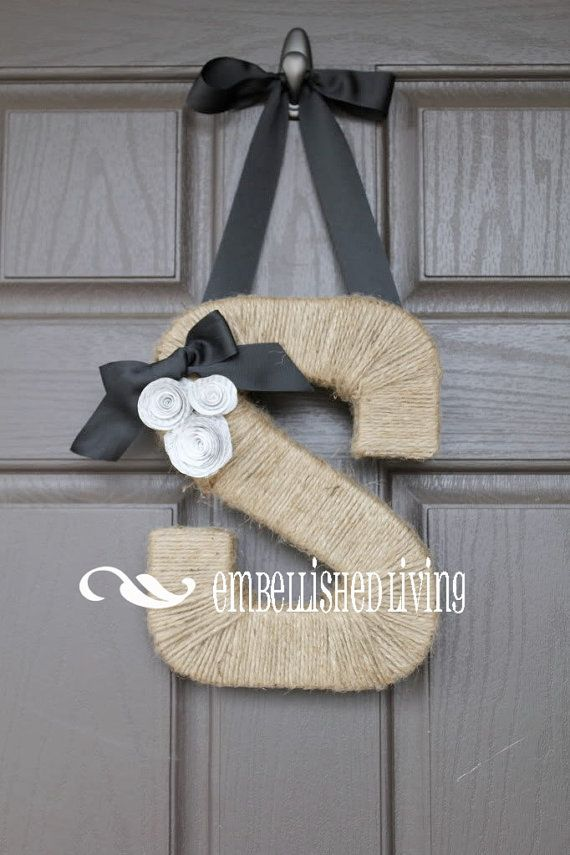 letter is handwrapped in natural jute and accented with a ribbon to hang, along with book paper rosettes topped by a matching bow