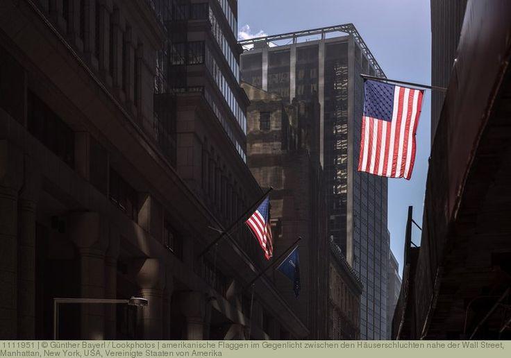 amerikanische Flaggen im Gegenlicht zwischen den Häuserschluchten nahe der Wall Street, Manhattan, New York, USA, Vereinigte Staaten von Amerika