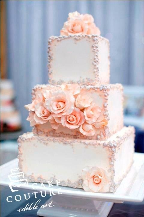 White wedding cake with silver edging and pink roses