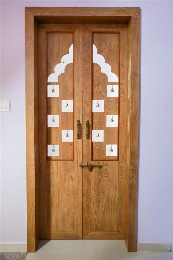 Innovative and attractive mandir door. bronze bells is used to make it more nice.