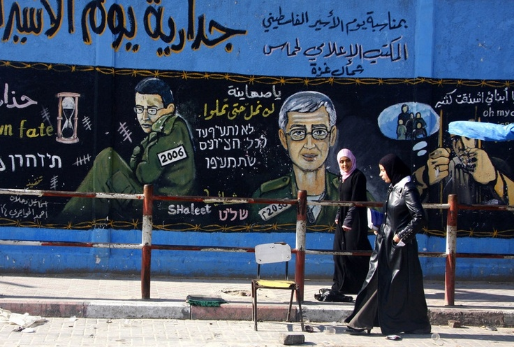 Gazan women walk past a mural of Israeli soldier Gilad Shalit who was captured by Palestinian militants in 2006