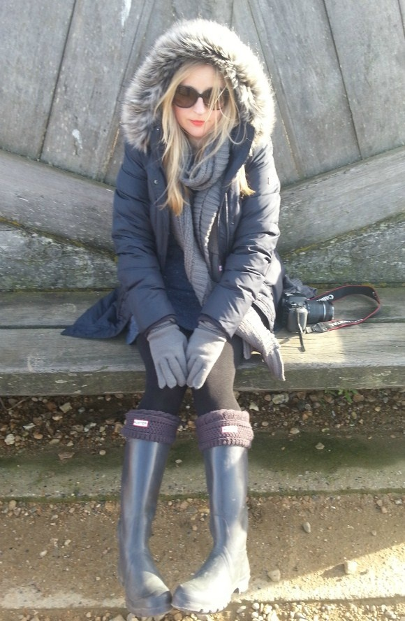 Sasha Wilkins from Liberty London Girl wearing 3/4 quilted down parka in navy, Original Tall wellies, Moss Cable Hat, Moss Cable gloves and Moss Cable Cuff Welly Socks.