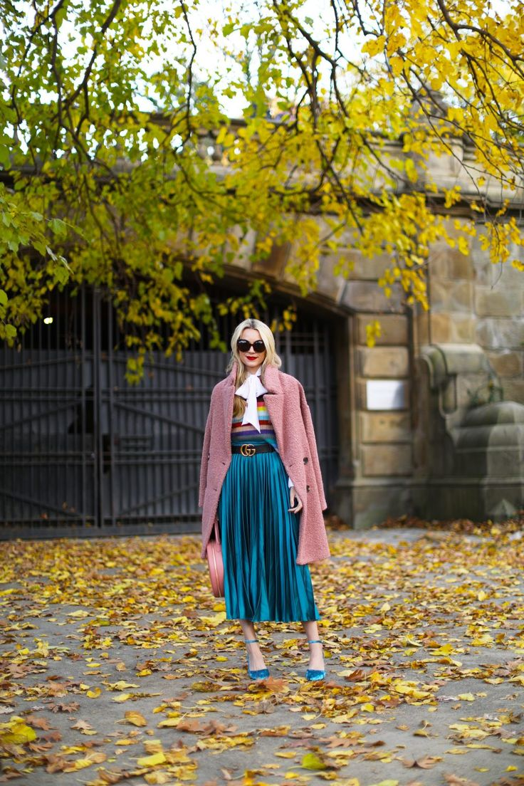 In rainbows with a bright blue/teal pleated skirt, blue heels, a pink jacket, and a striped sweater | Atlantic-Pacific