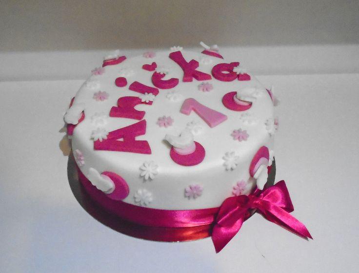 Dětský dortík obalený bílým fondánem, dozdobený fondánovými kolečky a kytičkami, saténovou stuhou a vyřezaným jménem.