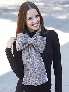 Add a romantic touch to any outfit with this charming bow scarf! (Yarnspirations)