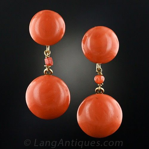 These rare, wonderful and quite striking 1 5/8 inches long drop earrings feature two pairs of sizable, deep salmon-colored coral buttons measuring 18 millimeters and 12 millimeters respectively (about 11/16 and 9/16 inch). The colorful ocean gems are punctuated by a small coral bead and are backed in 18 karat yellow gold; the larger coral dances freely below. The original clip backs are gold filled.