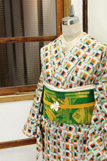 生成り色をベースに、ネイビー、オレンジ、グリーンなどのモザイクチェックデザインが織り出された正絹紬の袷着物です。
