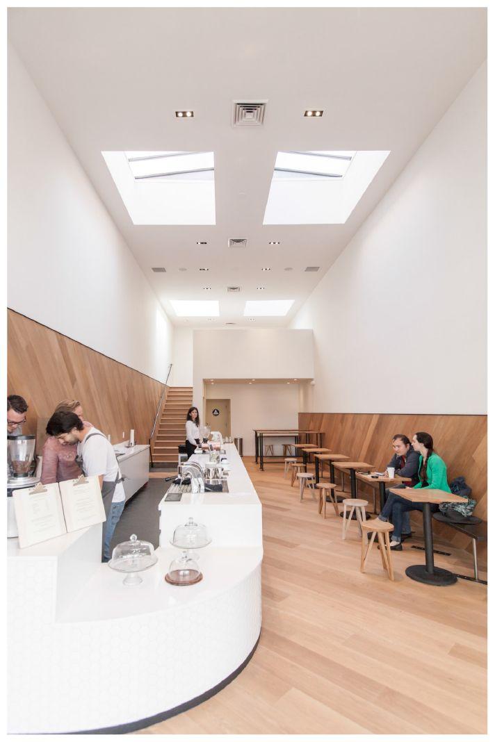 Essa cafeteria já se destaca desde a sua entrada: muita luz natural, madeira na parede e piso, e um balcão lindo, com azulejos hexagonais.