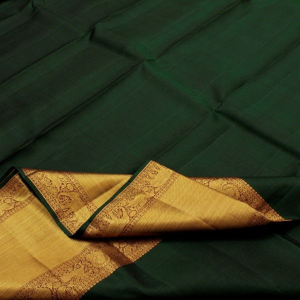 This #Kanjivaram silk #sari from Sarangi boasts of a bottle green silk body creating its own luster and sheen. The wide gold border is trimmed with a pinch of kumkum and woven yali, annapakshi, horse and elephant motifs. The pallu appears as if liquid sunshine has been spilt over a thali of powdered kumkum: traditional elephant and yali motifs add the signature touch. A maroon blouse adds to the elegance of this sari. For Kanjivarams in this alluring green, visit Sarangi. Code 120124680.
