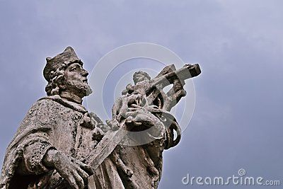Statue of John of Nepomuk with dark clouds in the background