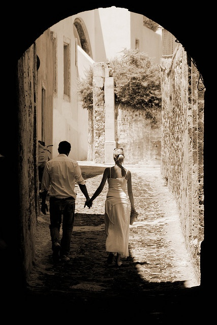 A couple walking hand in hand around the streets of #Santorini View On Black