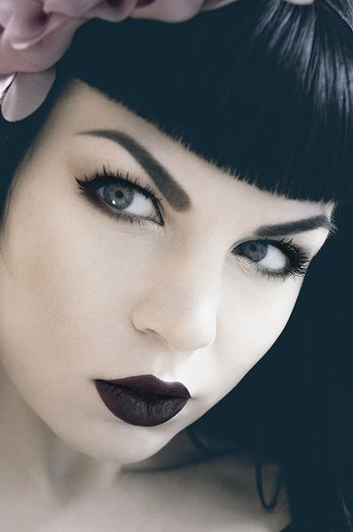 Black Betty Page style. I'm loving the dark with pale beauty. the slight color of her eyes and the flower in her hair make you realize its not a black and while photo.