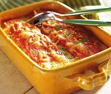 Korv under osttäcke som gratineras i ugn på en currykryddad bädd av grönsaker, tomatkross och grädde. Servera din currykorv direkt och njut!