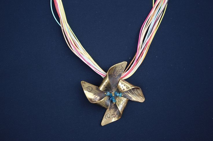 Copper pinwheel necklace hanging from 23 cords necklace