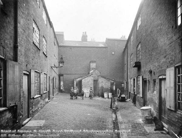 Parrott's Place, off Corn Street, 1931-2.  Like Parr's Yard, Parrott's Place was accessed through a small passageway from the main street. This photograph shows communal privies, a communal water pump, and a drain for carrying away waste water. Corn Street led north from Brook Street, towards the north-east of Nottingham town centre.