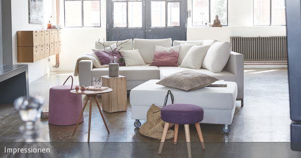 Wer sein Wohnzimmer gern in schlichten Farben wie Weiß und Grau einrichten will, wünscht sich oft den passenden Farbklecks dazu. Diese violetten Akzente dienen als Eyecatcher und verleihen dem Raum einen femininen Touch. So wird die Balance zwischen romantisch und modern gehalten, ohne kitschig zu werden.