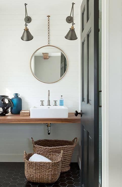 A black door opens to a modern cottage powder room filled with a wood floating vanity topped with a white porcelain sink and gooseneck faucet under a chain link mirror illuminated by black and gold swing arm sconces alongside a black hex tile floor.