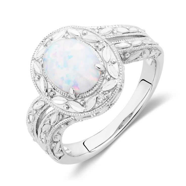 You will love the intricate design of this vintage style sterling silver ring. Featuring a created opal, and diamond detail, this ring has a unique look.