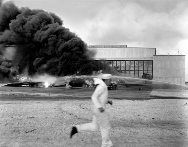 A sailor runs for cover past flaming wreckage hit by dive bombers that had already blasted Pearl Harbor and Hickam Field; Kaneohe Bay Naval Station.