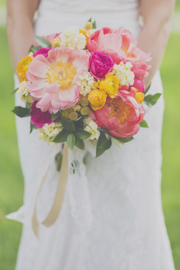 Bright pink and yellow bouquet filled with white blooms, ranunculus, craspedia and beautiful peonies | Photo: Blink of an Eye Photography | Bouquet: Floral V Designs