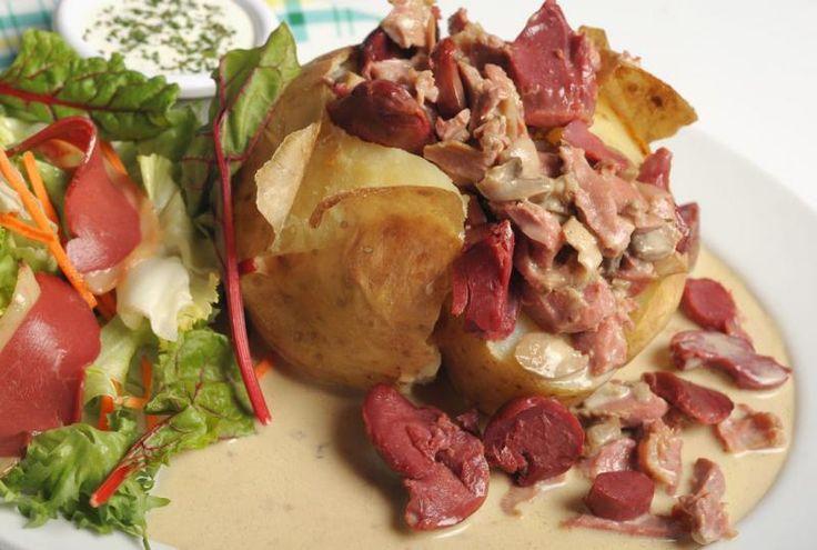 """Pom' au Four """"La Périgoudine"""" : Pomme de terre cuite au four, gésiers de volaille, champignons, magrets de canards fumés «I.G.P.» Sud-Ouest , sauce aux cèpes, sauce fines herbes et salade mêlée."""