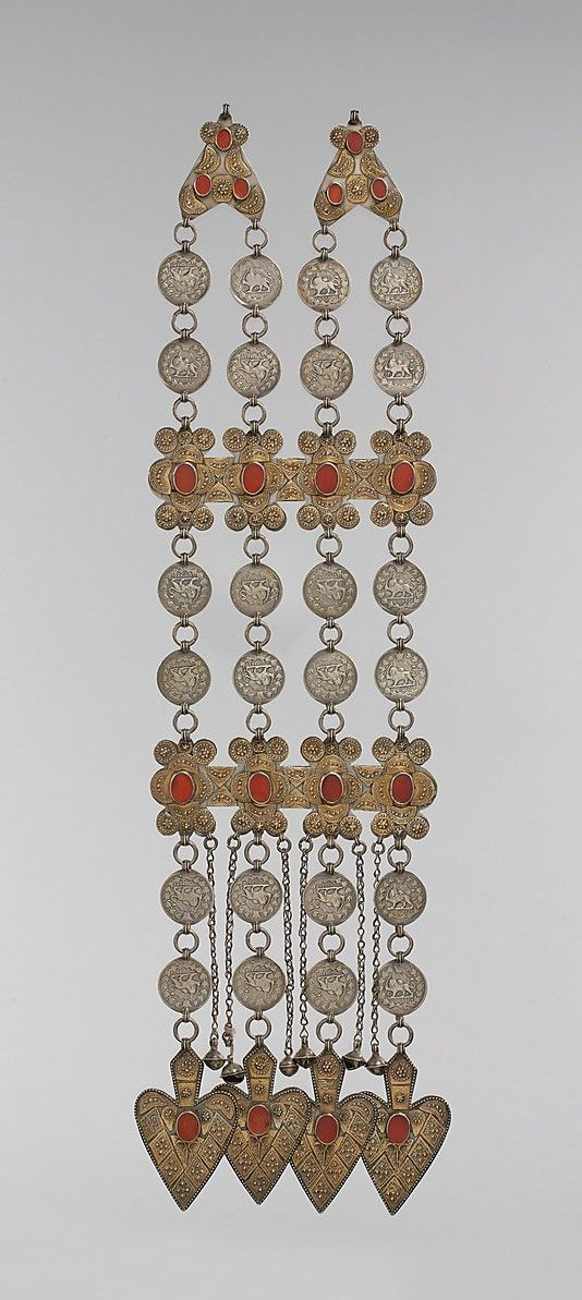 Dorsal plate ornament, silver; fire-gilded with stamped and engraved decoration, with dated Qajar coins, table-cut carnelians, chains and heart-shaped pendants. Central Asia or Iran, late 19th–early 20th century