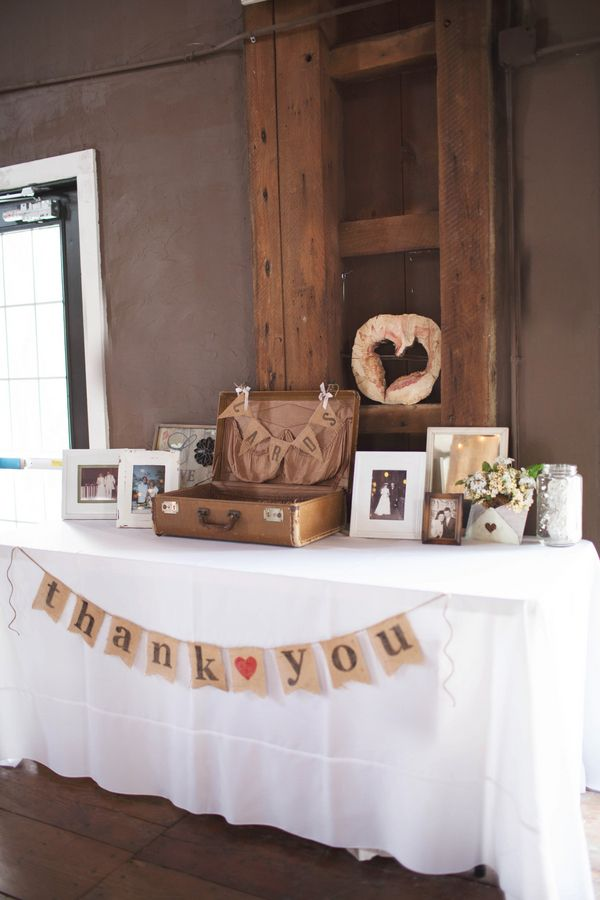 A vintage suitcase and burlap bunting decorated the gift table.  	Photo by Taylor Whitham Photography 	Venue: Mustard Seed Gardens