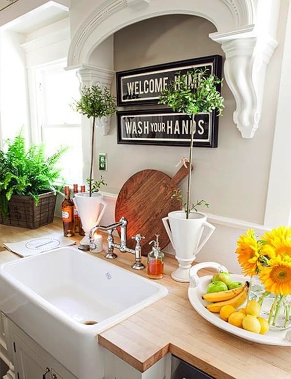 Great kitchen with gray walls, vintage sign art, white kitchen cabinets, butcher block countertop, farmhouse sink and topiaries.