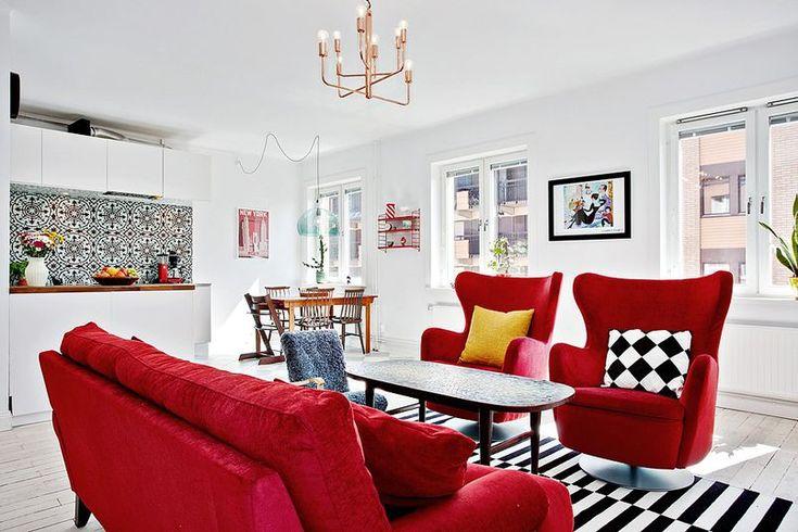 Sofa i fotele w czerwonej aksamitnej tapicerce są wyrazistym wyposażeniem tego skandynawskiego salonu. I prezentują się ekstrawagancko z czarno-białym pasiaStym dywanem i poduszką w romby. Nowoczesny żyrandol w miedzianym wykończeniu nadaje całości szyku w stylu glamour.